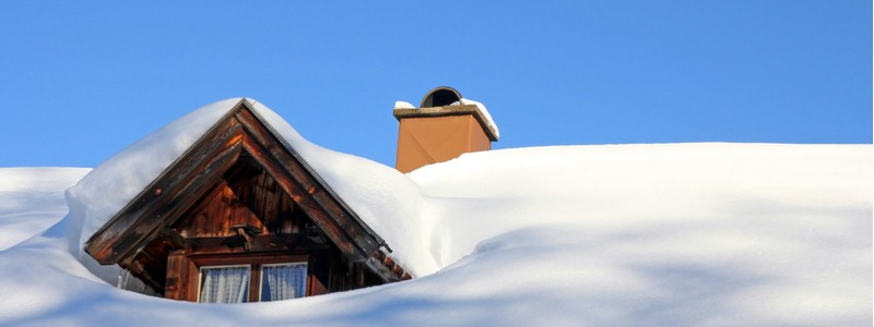 roof of wooden home completely covered in winter snow