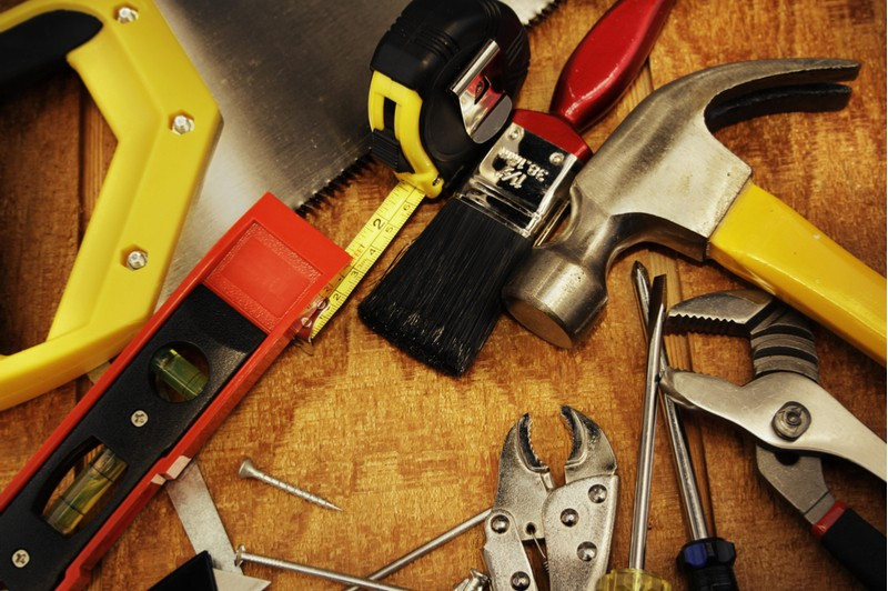 Home maintenance tools laid out on work table for display
