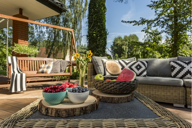 Outdoor patio with patterned pillows and bowls of fruit.