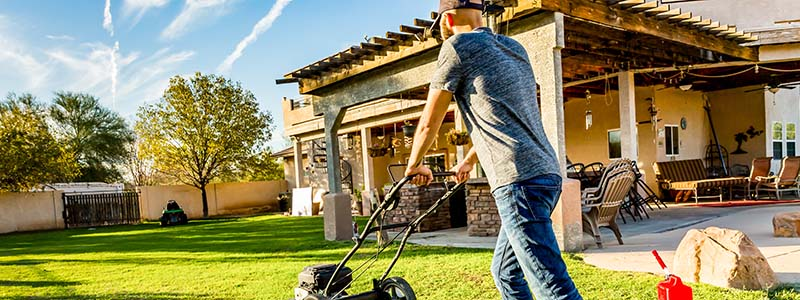 man mowing grass on green lawn