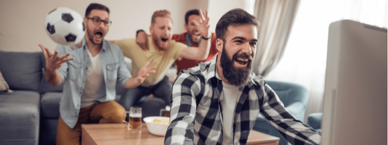Group of friends celebrating in front of tv in a living room.