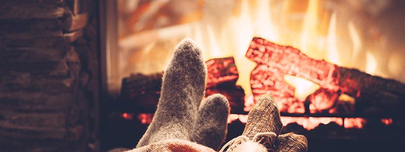 people in wool socks in front of cozy fireplace