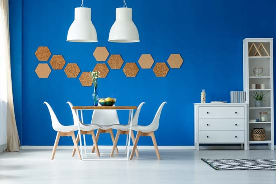 Dining room with white modern furniture and a bright blue accent wall.