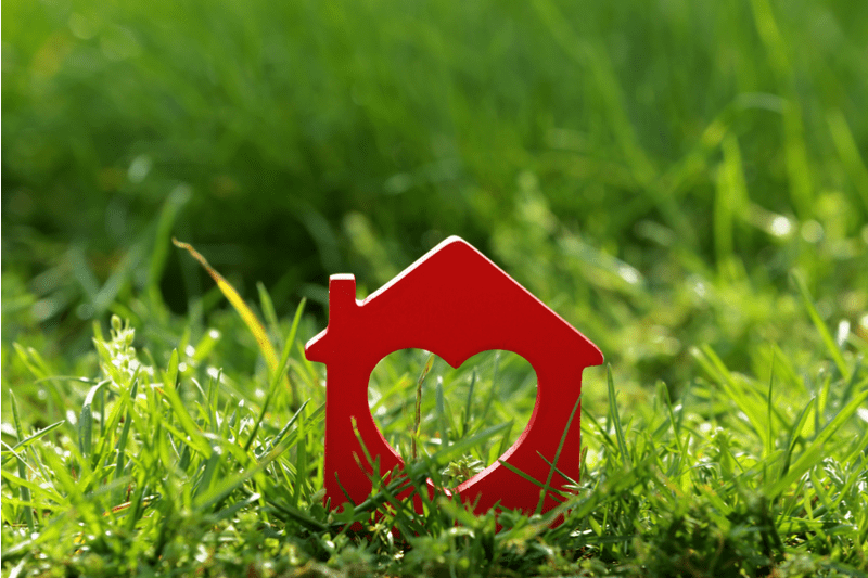 red house concept with heart shape carved through against a background of green grass