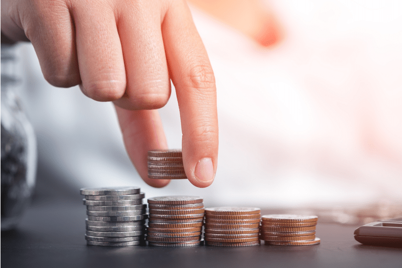 Female hand stacking coins to shown concept of growing savings