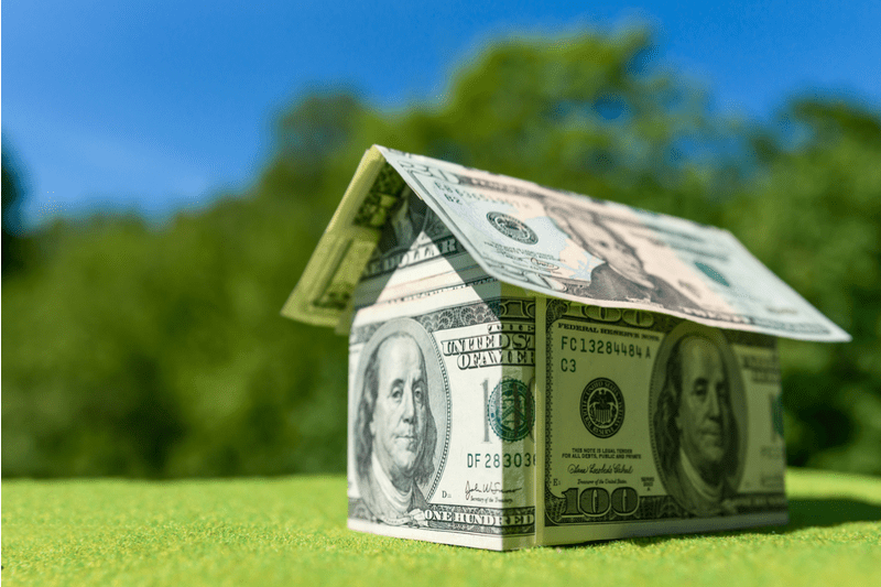 money folded into shape of house on grassy background