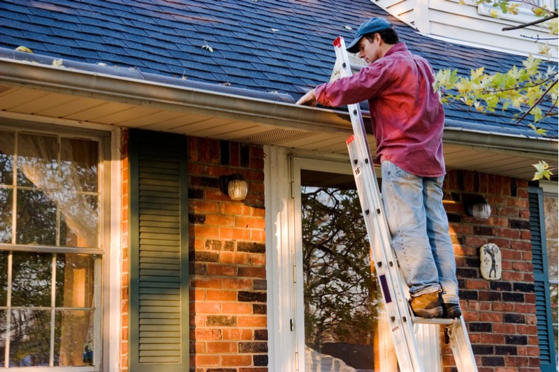 man cleaning out gutters on ladder