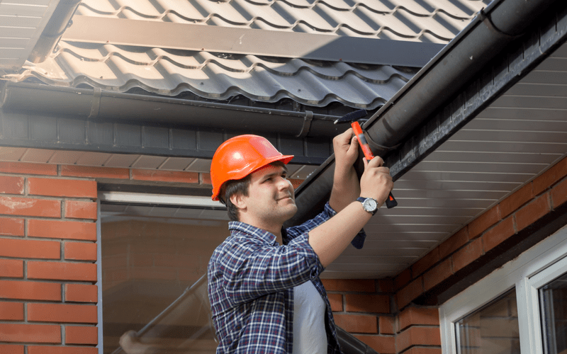 middle aged man in orange hard hat repairing gutter from a ladder