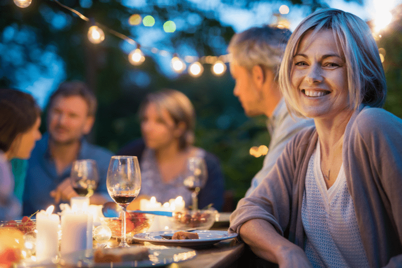 several people sitting at a patio table over dinner