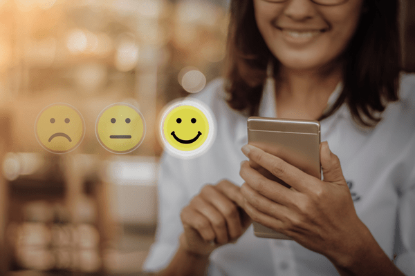 business woman using smartphone to rate an experience with a smiley face