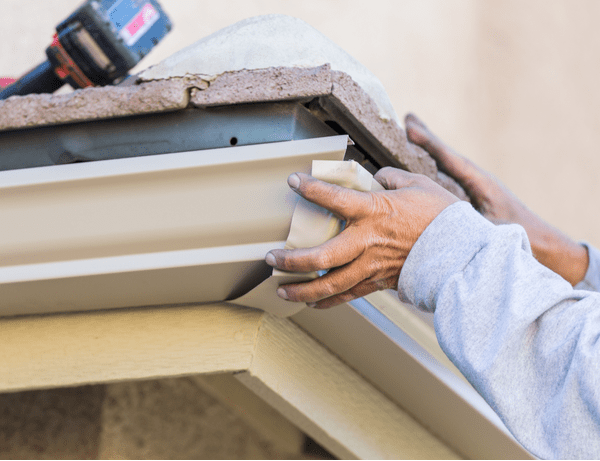 close up of tech's hands replacing corner gutter