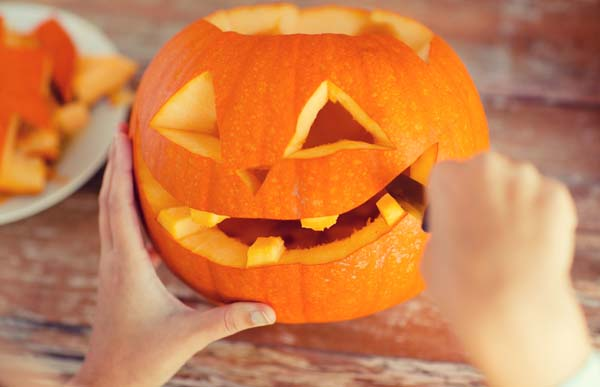 Person utilizing Halloween decorating tips to carve pumpkin