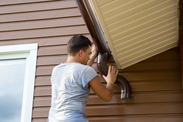 Man inspects gutter to look for repairs that may be needed