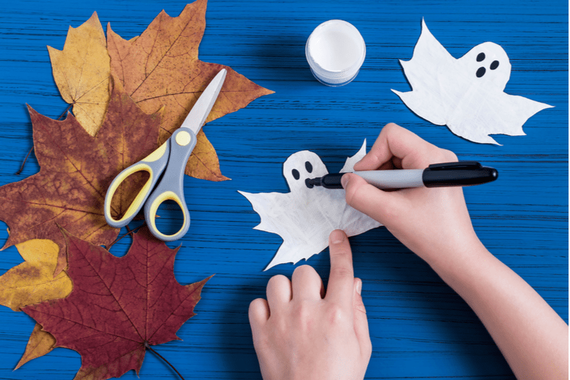 Hands creating ghost decorations based on leaf designs.