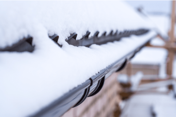 Gutters on house filled with ice and snow during winter.